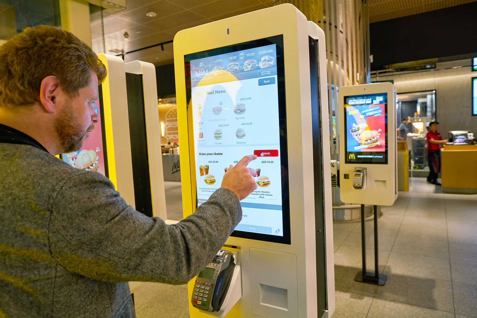 customer using self service kiosk and airport mcdonalds convenient ordering experience