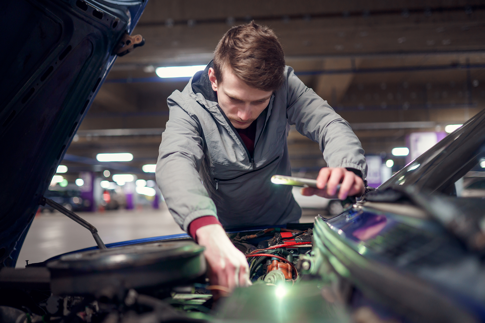 A young man watches a walkthrough video from a dealership while fixing his car.